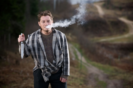 deranged: Young man in unkempt layered clothing, blowing cigarette smoke from his mouth, holding a knife at chest level in his right hand.  Taken in a rural setting.
