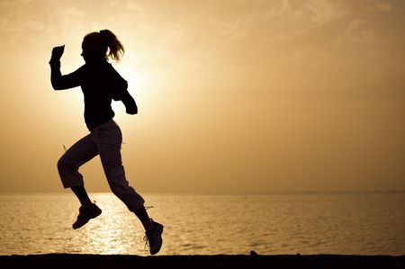 Young woman running on a sunset beach background Stock Photo