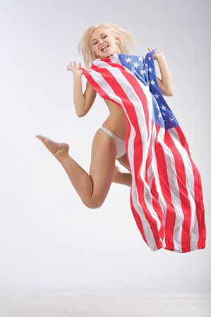 Jumping naked young woman in a USA flag Stock Photo
