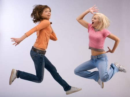 jumping two emotional women with rich color shirt photo