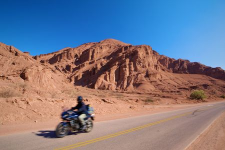 Photo unrecognizable person on a motorcycle. Motobikers on paved roads in the mountains of red against the blue, clear sky.