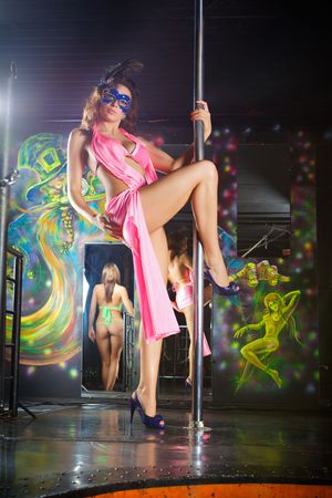 Woman with mask on face pole dancing in a nightclub.