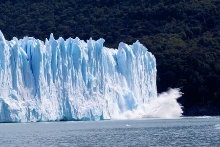 Image of a collapsing glacier ( Perito Moreno ) on a forest background.