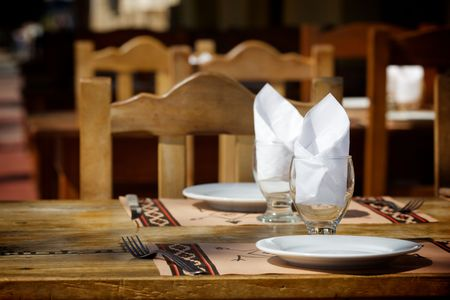 on the foreground: Two empty white plates, two glasses with napkins standing on a wooden table. Street restaurant.