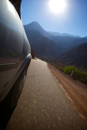 Photo of a mountain road with the passenger seat of a car. See the road (asphalt), car body, the mountains and the sun. Stock Photo - 6208931
