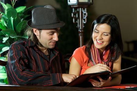 The beautiful girl chooses meal from the menu of restaurant together with the man Stock Photo