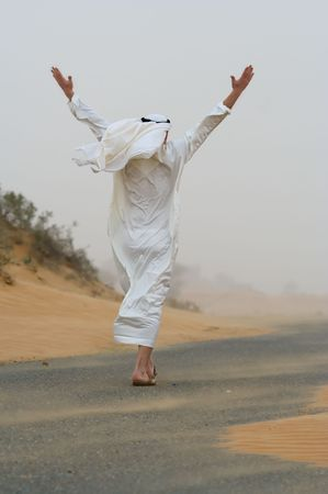 The back view of an Arab man, dressed in the traditional kondura, walking along a desert road amid a sandstorm. His arms are raised above his head.