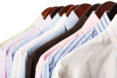 ropa colgada: Camisas de rack Close-up aislados sobre fondo blanco