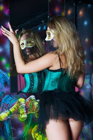 Stripper in the mask is a mirror in a nightclub Stock Photo