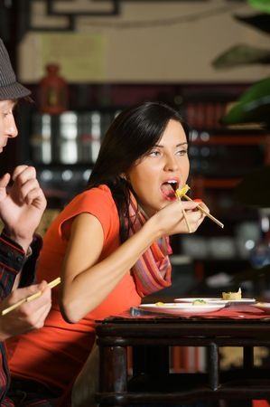 Beautiful young woman eating in Chinese restaurant. photo