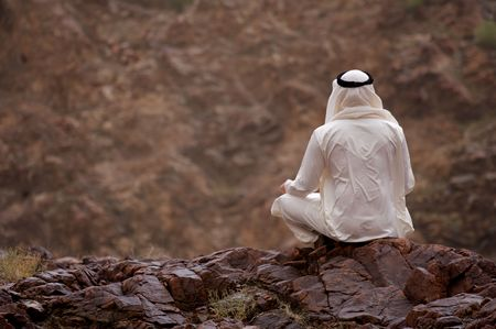 white robe: A view of a young Arab man sitting on a rocky overlook.