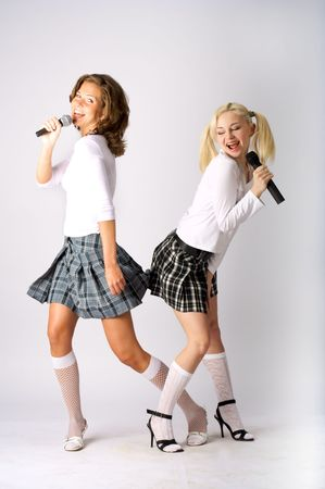 Two schoolgirls sing duet on a white background. Studio photos photo