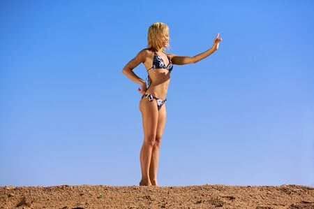 two piece bathing suit: Woman in bikini standing in sand. Stock Photo