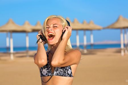 A view of a young woman singing loudly with the music she hears in her earphone on her iPod. photo