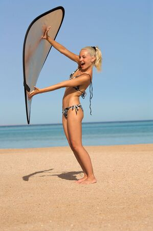 reflectors: A pretty blonde girl wearing a bikini on the beach. Shes playing with a reflector from a photo shoot.