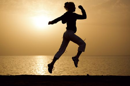 Young woman runs at a sunrise on a beach. Stock Photo
