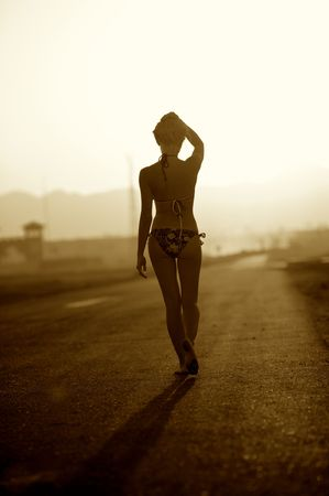 Woman in bikini go away on a background road