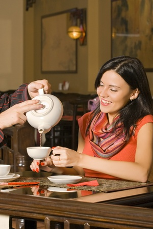 The young beautiful girl drinks tea at restaurant. photo