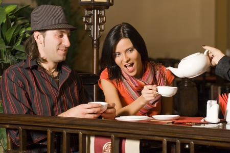 The waiter serves visitors. Behind a table at restaurant couple - the man and the woman. photo