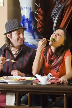 The young woman eats greens with chopsticks. The man smiles and looks at it. photo