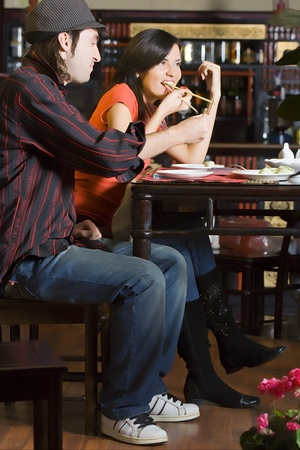 The guy with the girl eat at the Chinese restaurant behind a little table. A photo in full growth. photo