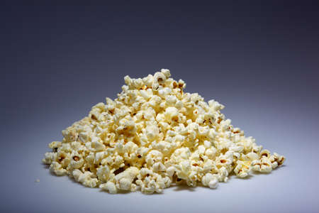 A pile of popped popcorn on a dark blue background Stock Photo - 11195398