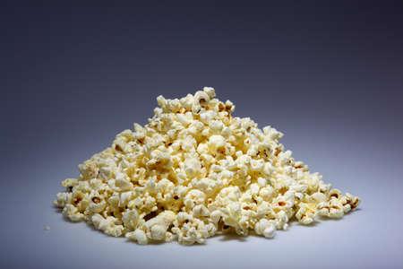 popped: A pile of popped popcorn on a dark blue background Stock Photo