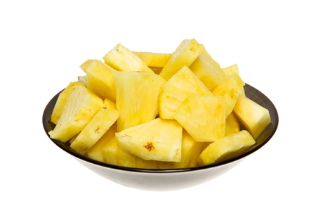 A heap of pineapple slice on black plate. Studio isolated on white background. Stock Photo