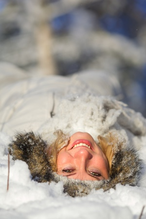 Happy young woman lying in the snow on their backs. photo