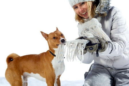 Beautiful young woman playing with dog. outdoor winter shot isolated on white background. photo