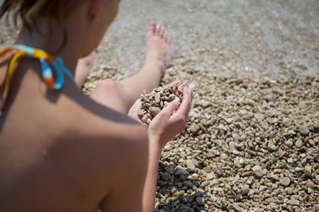 Photo from behind a girl in a swimsuit on a beach of pebbles. In the palms (hands) girl rocks. photo