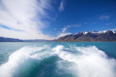 outboard: Picture trace of water from the powerful motor boats on the background blue sky and mountains with snow on top.