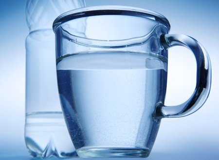 Clear water into a glass mug and  bottle on blue background. Stock Photo - 12917302