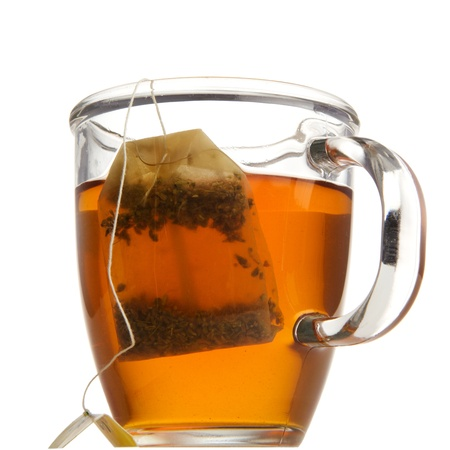 closeup on bags: Tea in a glass mug with tea bag. Studio isolated on white background.