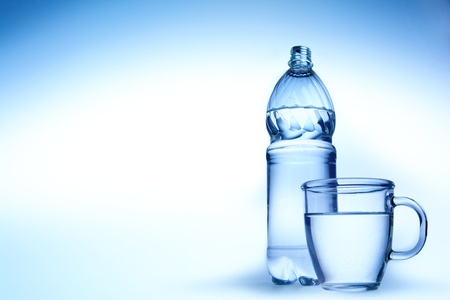 purified: Clear water into a glass mug and  bottle on blue background.