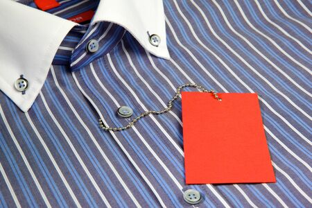 Blue mens shirt with white collar and empty red label on iron rope photo