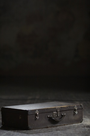Image of old suitcase lying on the wooden floor