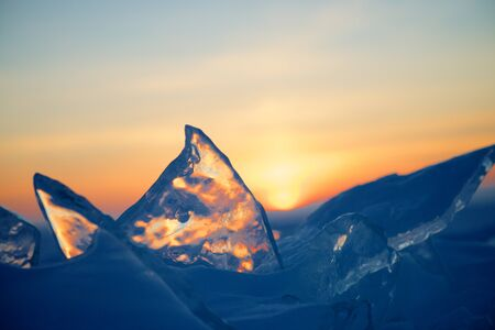 Sunset on a background of clear ice