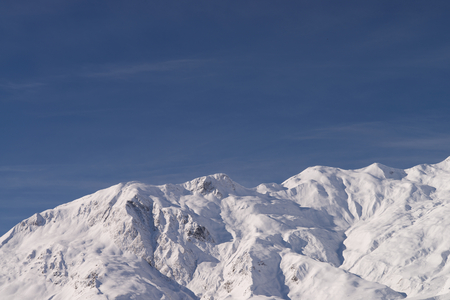 Low sun in Winter on snow covered mountain range with deep crevasses and gulleys, dark blue sky background. Stock Photo