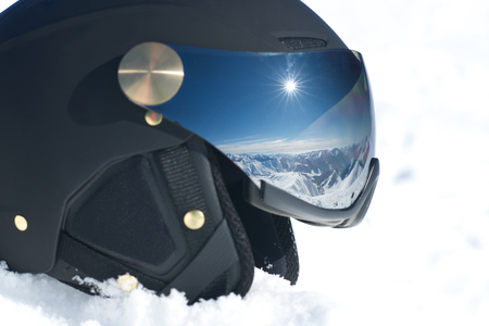 Reflection of mountains, blue sky and sun in sunglasses on the black helmet in the snow.