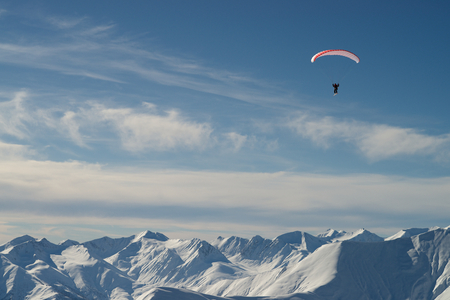 Paraglider over snow mountains