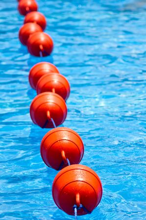 separating: A pool divider resembling a vibrant catterpillar Stock Photo