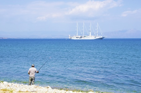 A man fishing and a sailing ship crosses by Stock Photo - 15628711