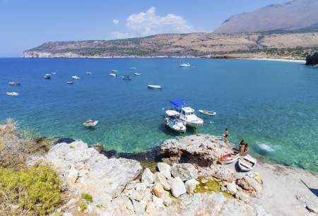 embarked: Boats embarked and people swimming by the shore near Dilos caves in Greece  Stock Photo
