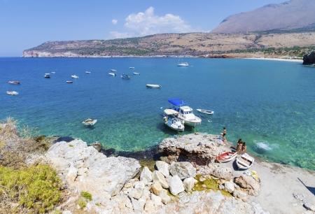 eingeschifft: Boote eingeschlagen und Menschen schwimmen am Ufer in der N�he Dilos H�hlen in Griechenland Lizenzfreie Bilder