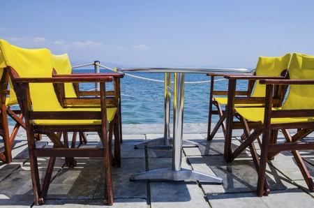 A coffee table with yellow chairs next to the beach Stock Photo - 15629640