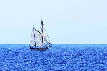 A sailing boat crossing the sea ocean photo