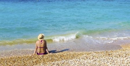 A woman wearing a hat, sitting on the beach staring at the sea Stock Photo - 15730231