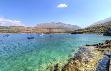 The beautiful Greek coastline with crystal clear waters and many boats anchored near Diros caves in Greece. Stock Photo