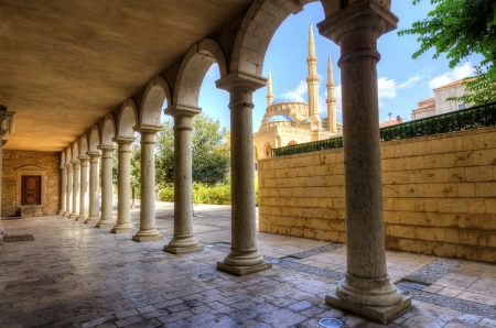 The Mohammad Al-Amin Mosque situated in Downtown Beirut, in Lebanon as viewed through the pillars of the Greek Orthodox church of St George  photo